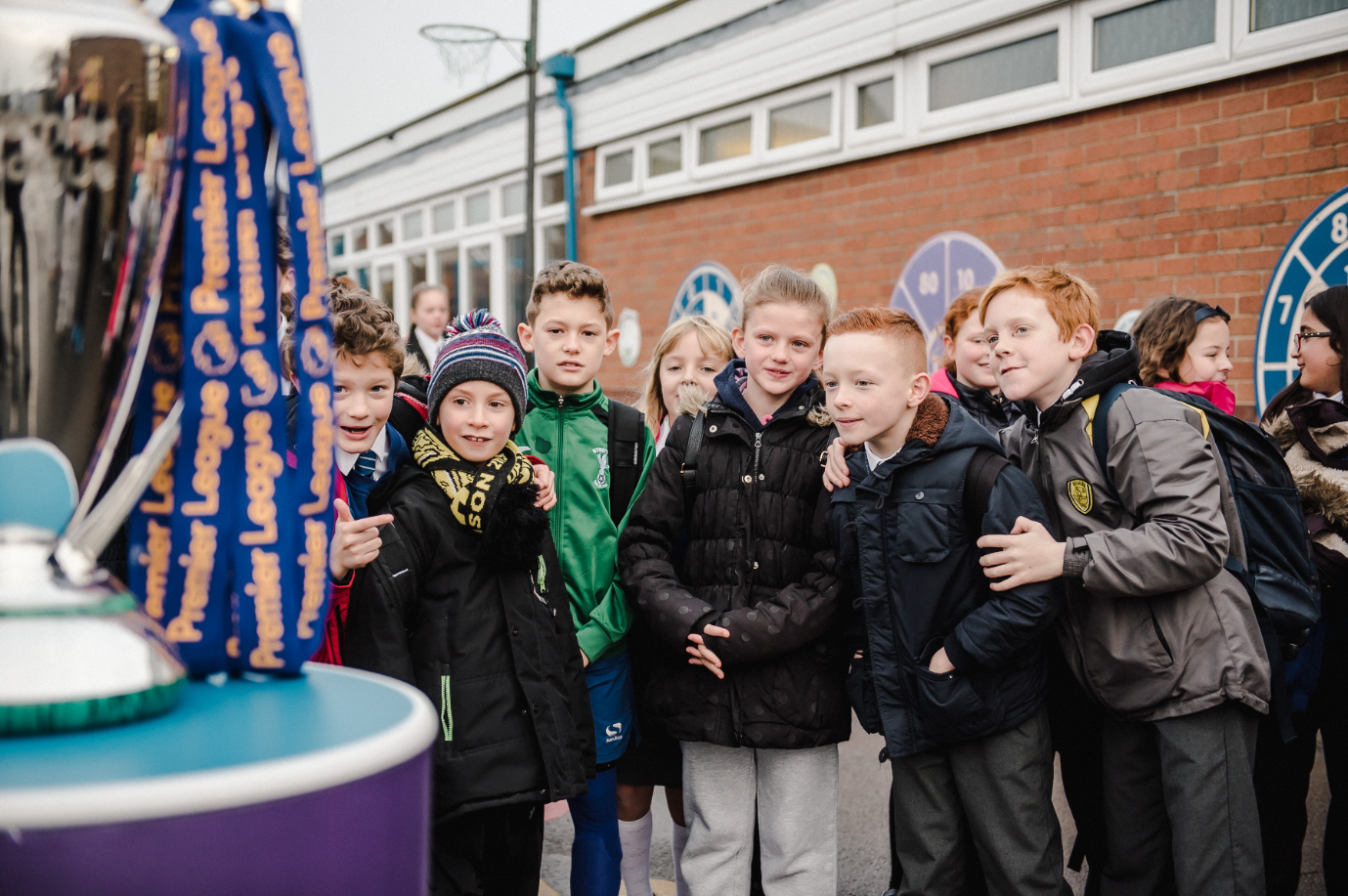 Children looking at the Premier League trophy